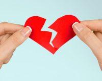 two hands holding a shape of a broken heart
