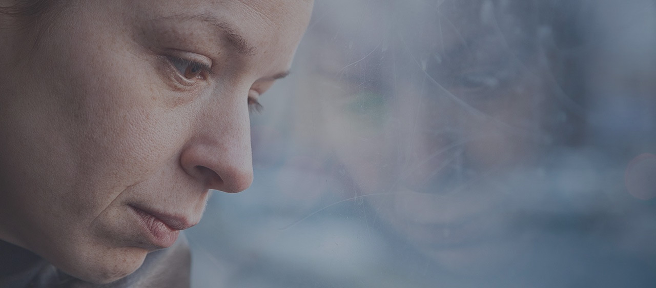 woman looks sad and thinking looking outside a window
